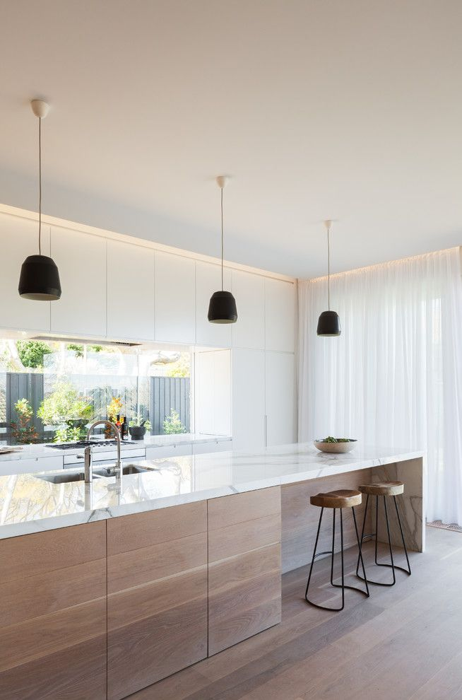 The white counter top creates a lovely modern, chic look for your kitchen. Complete with the low hanging ceiling lights...we love this look!