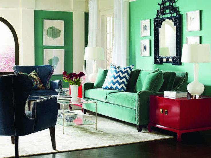 idée déco salon éclectique avec coussins décoratifs, canapé vert, tapis blanc et meuble de rangement rouge laqué