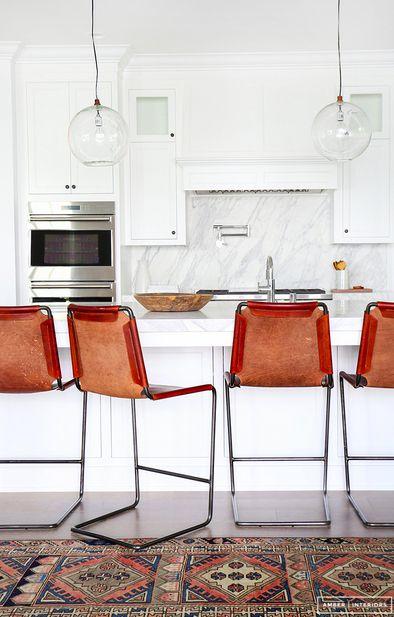Orange leather & the tribal print rug break up this white-on-white kitchen nicely.