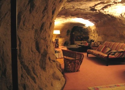 This 1,650 square foot, one-bedroom cave home carved from a 65-million year old sandstone formation 280 feet above the La Plata River is furnished with plush carpeting, Southwestern style furniture and accents, hot and cold running water, a well-appointed kitchen including microwave and washer/dryer, cascading waterfall-style shower, and a flagstone hot tub!