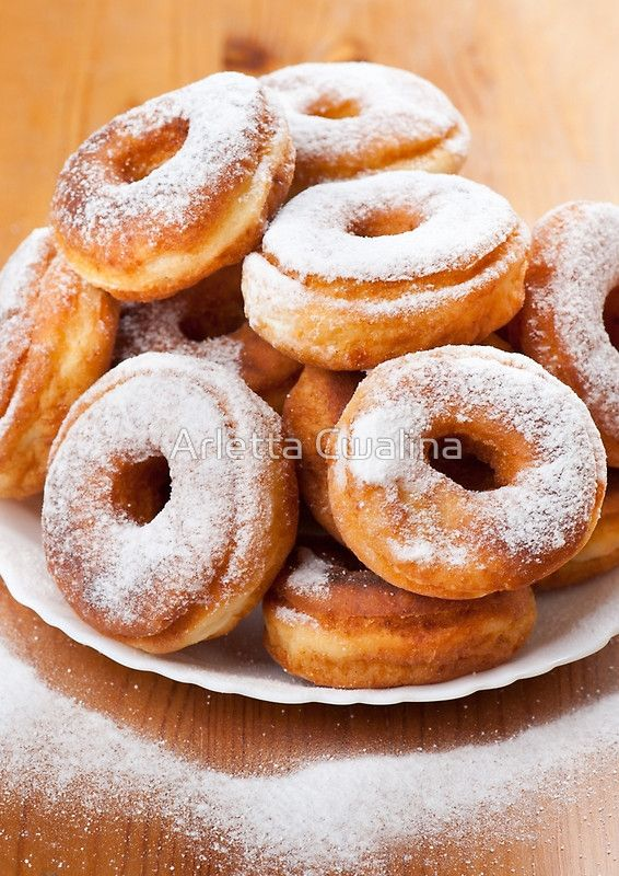 Pile of sweet donuts with holes and powdered sugar lying on white plate on table, objects in studio shot. #doughnuts #food #sweets #sugar #dessert #calories #donuts #fried #homemade #tidbit #notebook