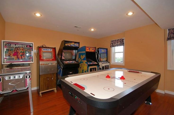 Contemporary Game Room with Asteroids Arcade Game, Hardwood floors, High ceiling, Bally Playboy Pinball Machine