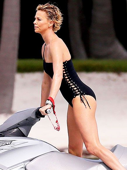 CHARLIZE THERON  Black one-pieces don't traditionally get tongues wagging, but Charlize changes that with a unique one-shoulder bathing suit that features a sexy lace-up design on one side. Let's just hope she slathered on the SPF while riding the waves in Miami
