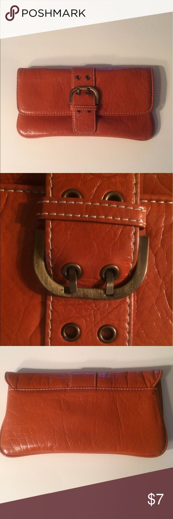 Burnt orange clutch with buckle detail. 10 inches across.  5.4 inches tall.  Snap closure for security.  Zipper pocket inside.  Metal buckle looks tarnished.  No rips. Not leather.  Feels like vinyl.  Pretty  color. Bags Clutches & Wristlets