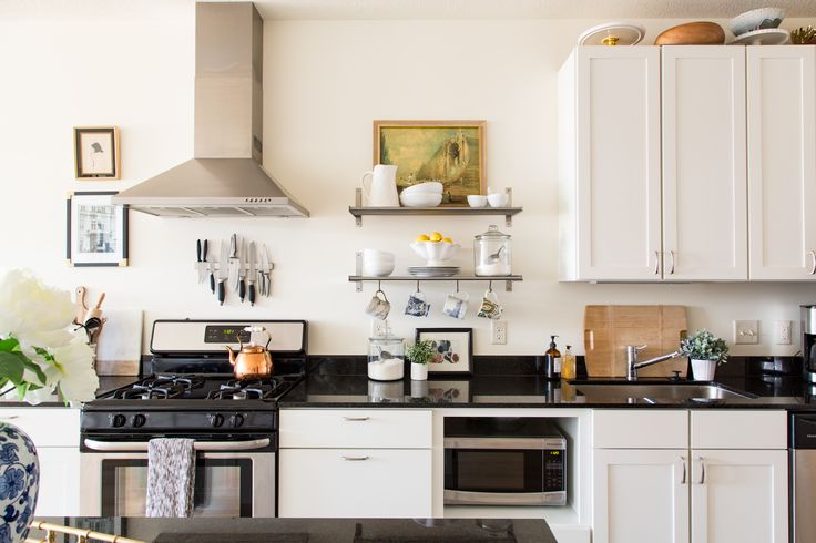 """""""The white kitchen was also a selling factor. I love white kitchens because they just look clean and bright."""" The copper tea pot sitting on the stove was found at an antique store."""