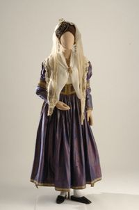 The bridal costume from Lefkas starts with an ankle-length chemise, which has white-work embroidery on the cuffs and dickey. Fastened beneath the breast is a cane or wooden stay covered with fabric. Three full-skirted gathered petticoats are attached at the waist. Over all this goes a silk dress with a long-sleeved bodice that barely covers the breast and a long full skirt that covers the chemise. A long ependytis (coat) is worn over the dress, topped with a square, cream-colored silk scarf…
