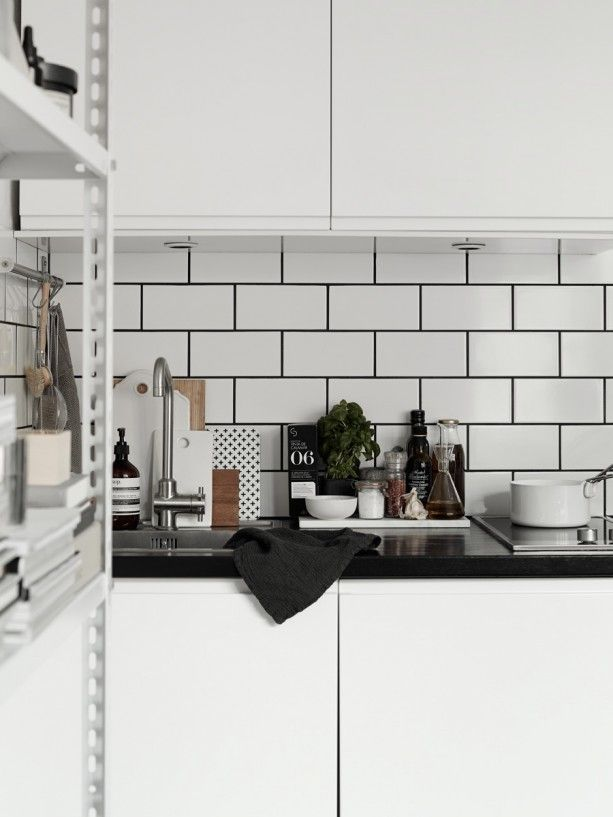 black counters, white subway tiles with dark grout. white uppers and lowers. faucet.