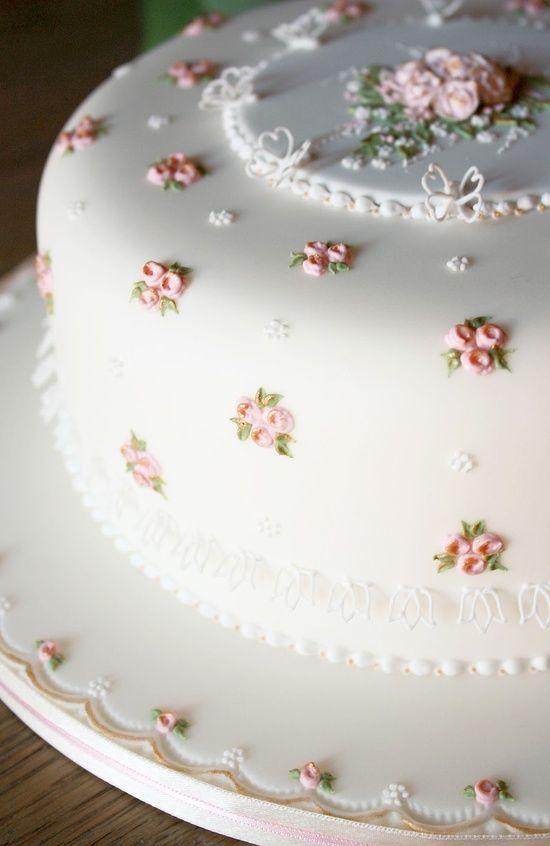 Fondant cake with tiny frosting flowers. I only like the little flowers, not the big one in the middle.