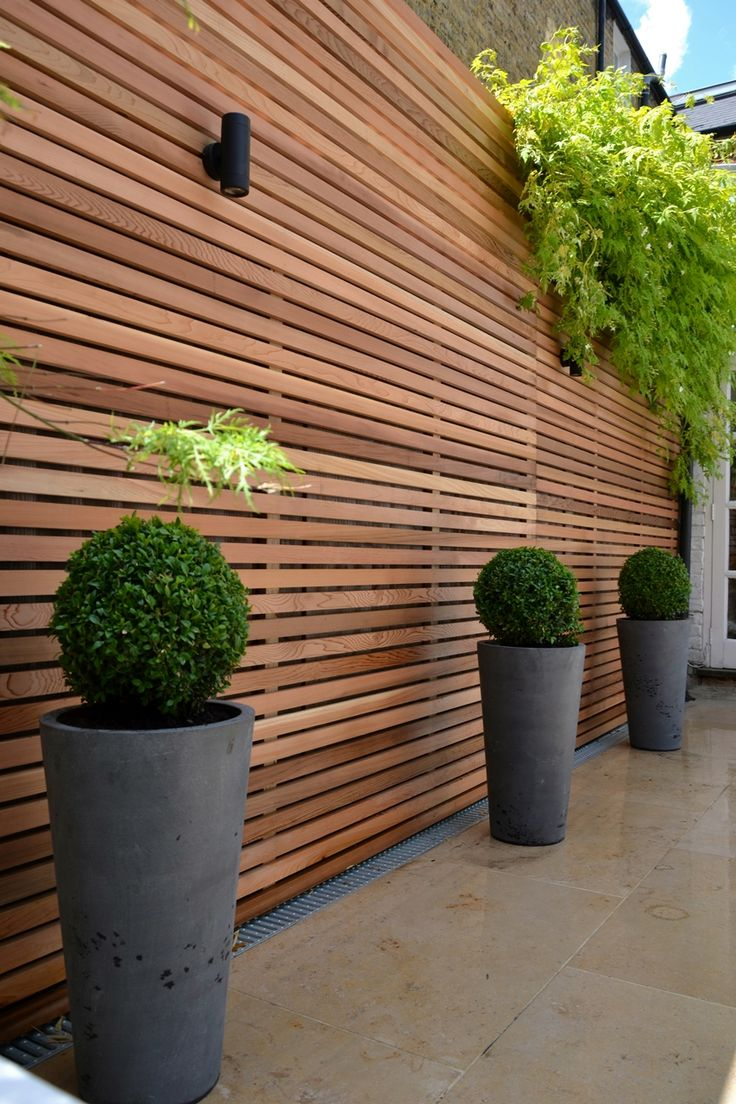 Great light fixture. Cedar timber batten cladding privacy screen trellis with grey stone pots buxus balls and Jura Limestone paving, London. (Click on photo for larger image.) Photo found here: http://rhsblog.co.uk/2012/07/02/cedar-timber-batten-cladding-trellis-privacy-screen/