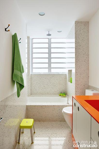 Para o ambiente das crianças,os arquitetos escolheram uma bancada de Corian laranja e revestiram meia-parede e piso de um padrão de Silestone que lembra o granilite original do apartamento.
