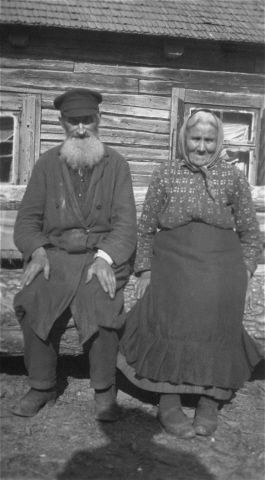 Portrait of an elderly Jewish couple sitting on a log in front of their home in a Lithuanian village.