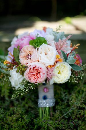 Bridal bouquet of peach juliet cabbage roses, coral charm peony, white cabbage roses, astilbe, lambs ear, nandina berry, asclepsia, and viburnum berry
