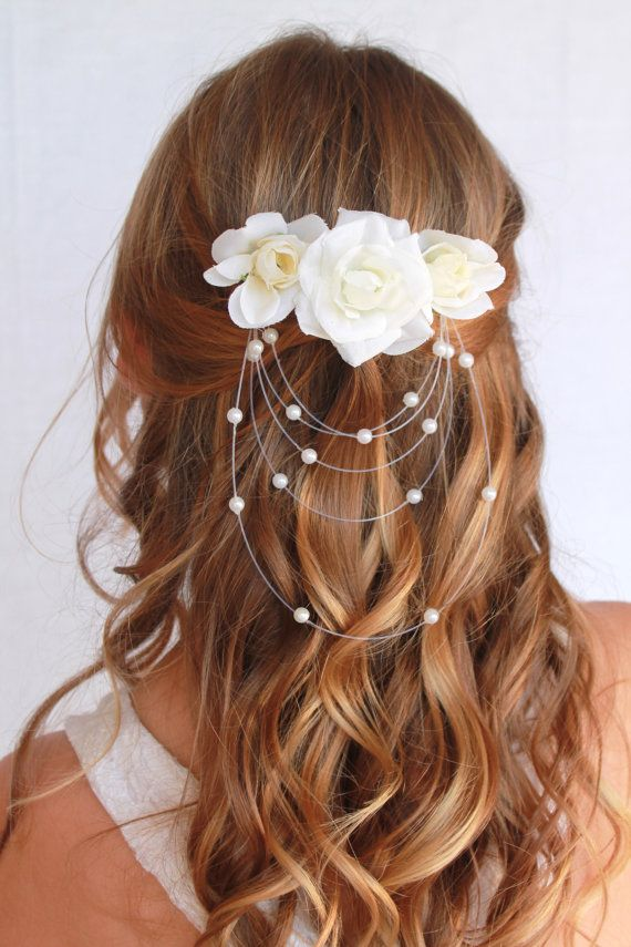 """This breathtaking floral comb features a stunning row of white roses, with an attached faux-pearl """"veil"""" and mounted on a silver hair comb. This"""