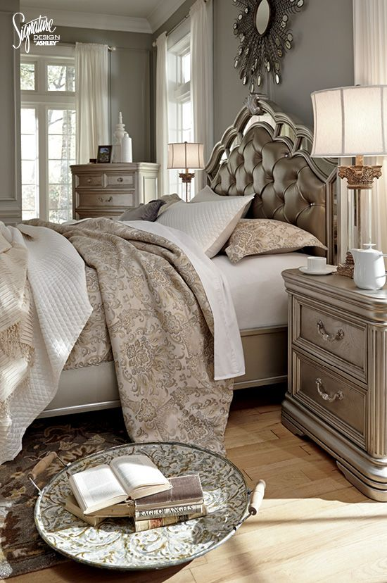 LOVE this glam bedroom! Sophisticated shades of beige, silver, and ivory combine to create the perfect luxurious bedroom oasis! From the upholstered and mirrored headboard and footboard, to the layers of cozy bedding, to the elegant finishing touches, this is definitely a statement-making style! Featuring the Birnally Bedroom suite - Ashley Furniture - Signature  Design by Ashley - #AshleyFurniture #GlamBedroom
