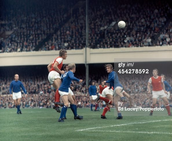 News Photo : John Roberts of Arsenal heads the ball over Denis...