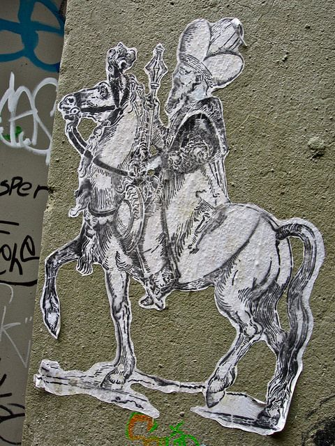 Medieval-looking wheatpaste street art, seen on a wall in Seattle, Washington. Is this a bishop, or Don Quixote