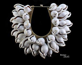 Een grote ovale ketting van Papoea-Nieuw-Guinea van wit gevlochten touw, versierd met twee banden van zilver schelpen. De binnenste band van de ketting is versierd met een lijn van rode houten kralen. De grootste zilveren schelpen zijn 2,8 inch in lengte en de kleinste 2 inch in lengte. De binnenbreedte van de ketting is 5 inch, en de buitenste breedte is 14 inch. De ketting heeft een lengte van de daling van 12 inch en is gekoppeld, aan de top, door een wit gevlochten touw loop, en een…