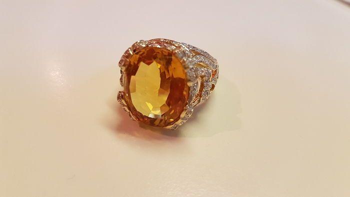 Gouden ring met Citrien en diamanten  14 k gouden ring. Opengewerkte ontwerp aan de zijden in de vorm van linten en strikken ruimschoots instellen met diamanten. Een grote ovale gefacetteerde Citrien ligt boven.14k Rose gold; 167 gr; 255 x 192 x 32 4mm; maat 20mm - ovale gefacetteerde Citrien; 1925 x 15 45mm; 13ct  diamant briljant geslepen 0004 ct x 172 pcs (= totale 0688 ct); Si - P1 kwaliteitEdelstenen worden vaak behandeld om de kleur en de helderheid te verhogen. Dit is niet onderzocht…
