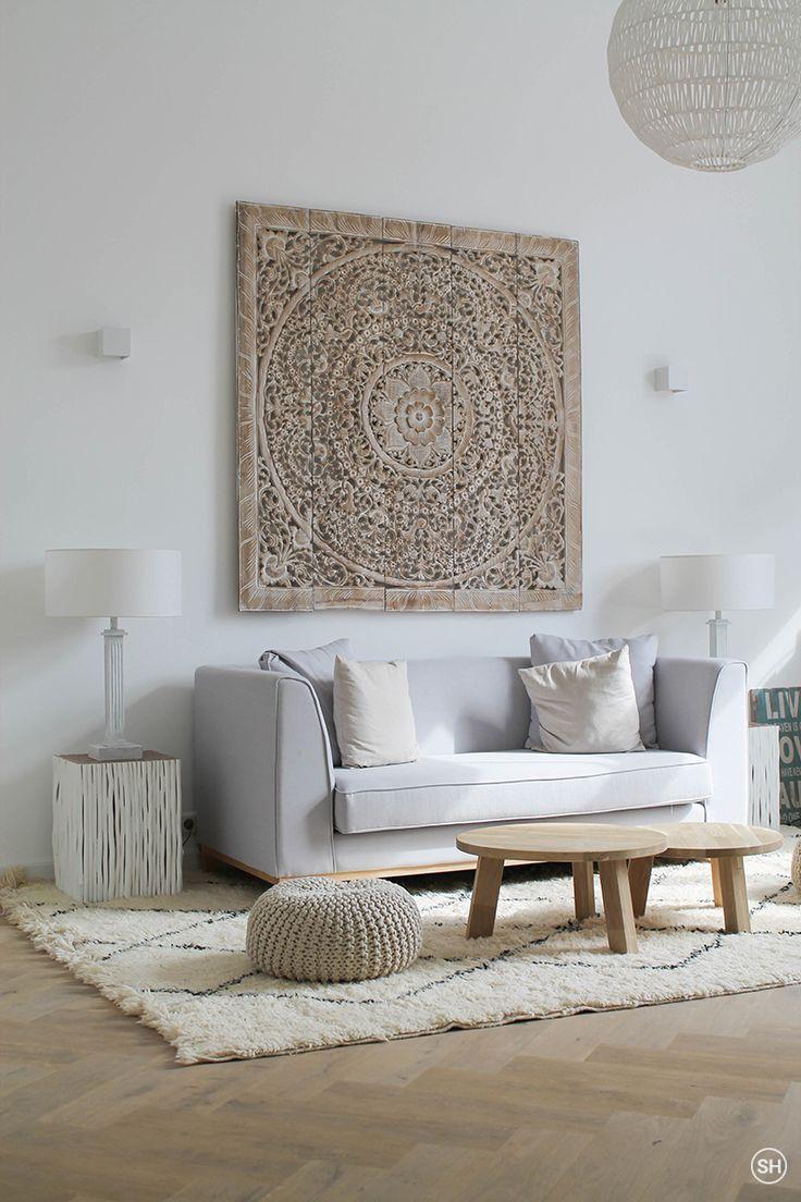 Een mooi houten ornament aan de muur geeft super veel sfeer. En leuke, niet te grote, bijzet tafeltjes of gebreide poef.