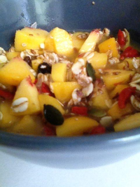 Jezelf verwennen met een goed ontbijt van fruitmuesli met verse sinaasappelsap, stukjes perzik, goji bessen en pompoen pitten