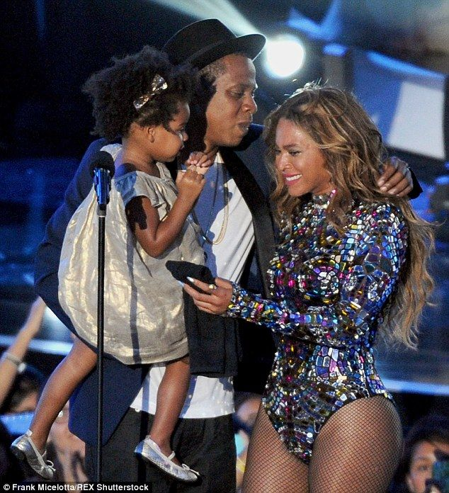 Flawless: Jay Z, carrying the couple's daughter Blue Ivy, presents Beyoncé with an award at the 2014 MTV Video Music Awards