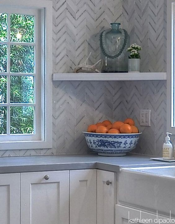 Stunning kitchen with white shaker cabinets paired with zinc countertops and a white and gray marble herringbone pattern tiled backsplash that goes all the way to the ceiling. A corner floating shelf lines the backsplash next to farmhouse sink.