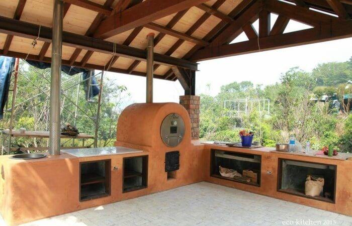Bela cozinha ecológica ao ar livre, com fogão a lenha em forma de barril. Construído por David Liu em Taiwan.  Fotografia: Rocket Stove Science.