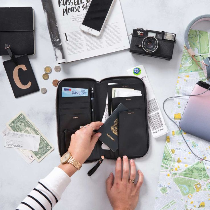 Travel essentials including passport wallet, luggage tag, tech case