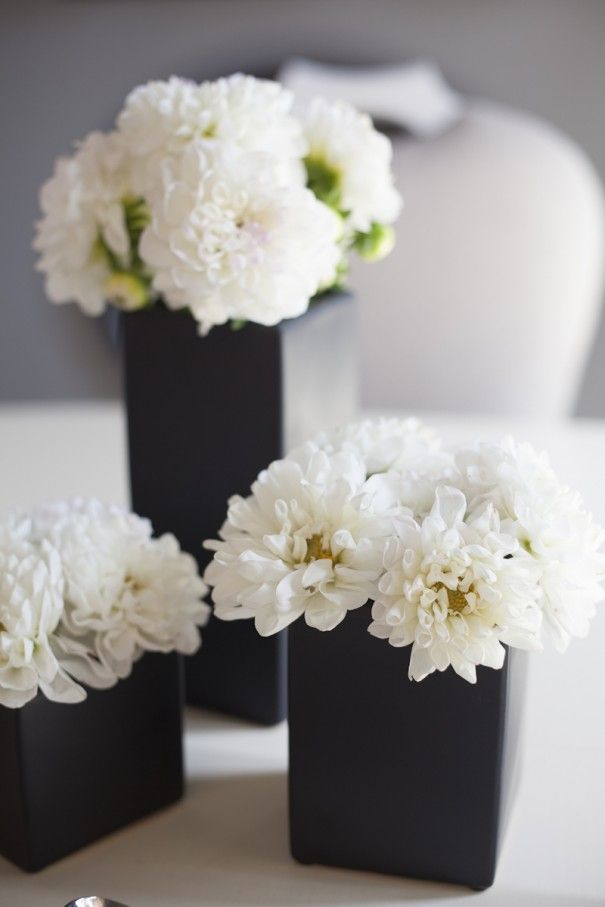 Wonderful color contrast of simple white blooms in small black vases.