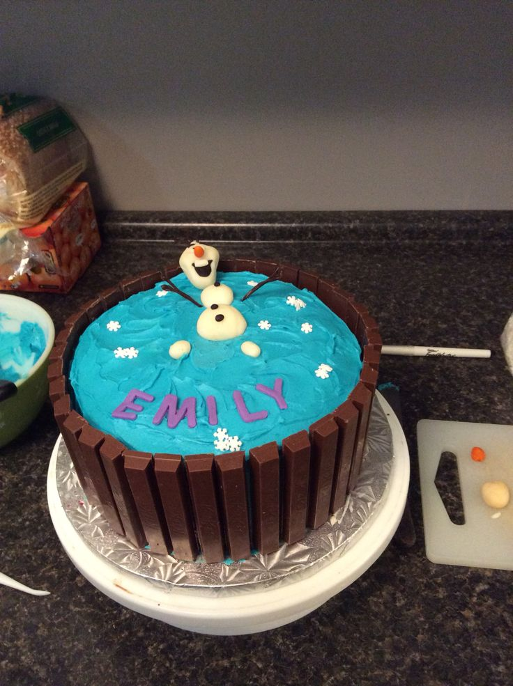 Emily's 3rd birthday. Chocolate cake filled with raspberry jam and mock cream icing. Kit Kats around the outside olaf made out of edible moulding dough.