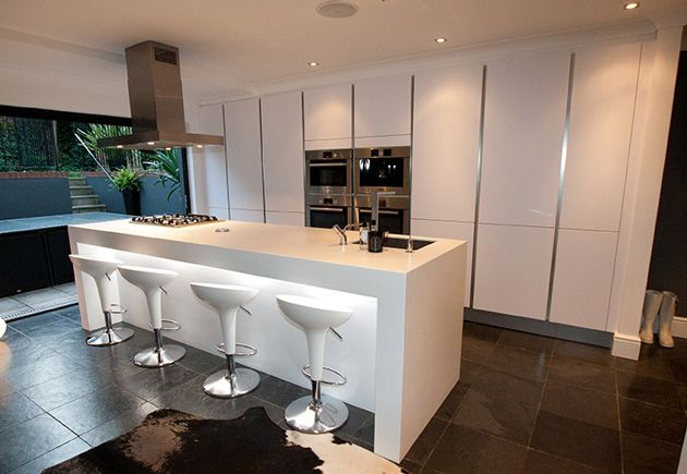 This contemporary high gloss island kitchen design is finished in a Polar white high gloss satin lacquer. The Polar white is sharper than other whites and in this design lighting integrated within the breakfast bar effectively shows off its crisp and sleek finish.
