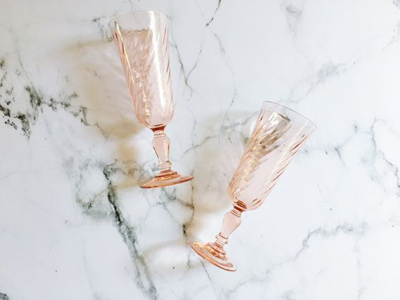 This pair of gorgeous, vintage, pink glasses were very possibly made by the Arcoroc company in France sometime during the 20th century. The stand elegantly with a swirled texture around the body of the glass with a shorter, curved stem on a sturdy base. Their elongated style lends them for use as champagne glasses though they could also be used as wine glasses or cocktail glasses. As a pair they would be fun as a gift for a bride and groom for toasting glasses at a wedding or for personal…