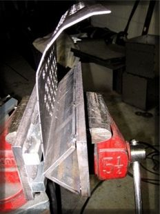 Press Brake - Homemade press brake constructed from angle iron, steel plate, and square rods mounted on a bench vise.
