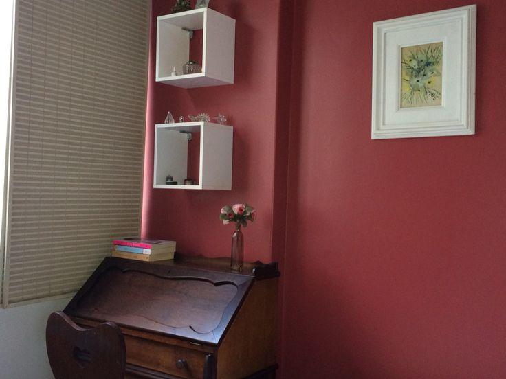 Contraste de madeira escura com nichos brancos e parede cor groselha(suvinil)