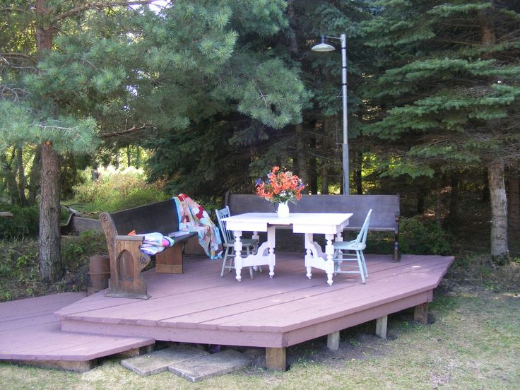 Raised deck from old lumber , recycled paint - decorated with old church pews and furniture I painted.