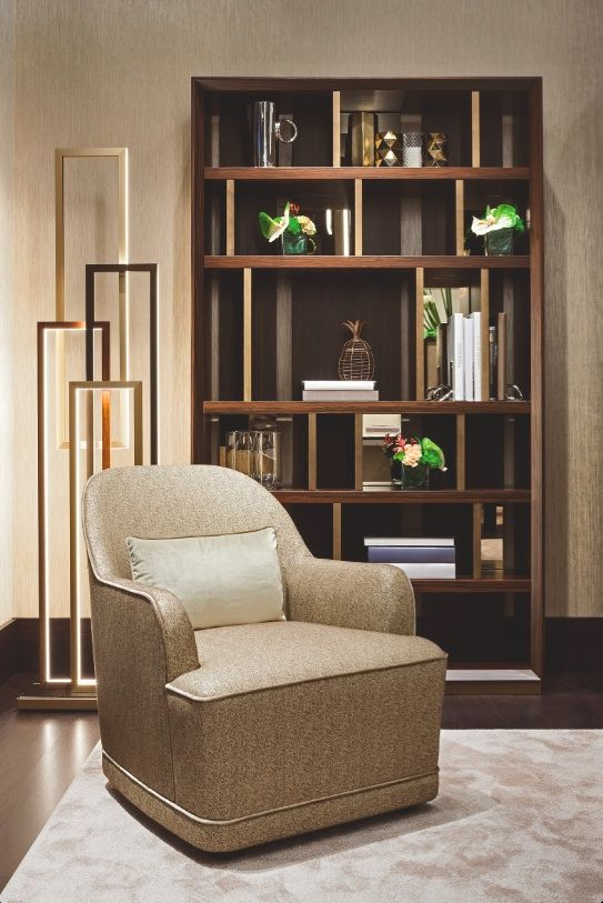 "The ""Symphony in Beige"" living and dining room by Oasis features a Magritte bookshelf, perfect for book of any size, a Dauphine armchair, covered with fabric with special texture and an Edge floor lamp, for a dramatic Art Déco effect."