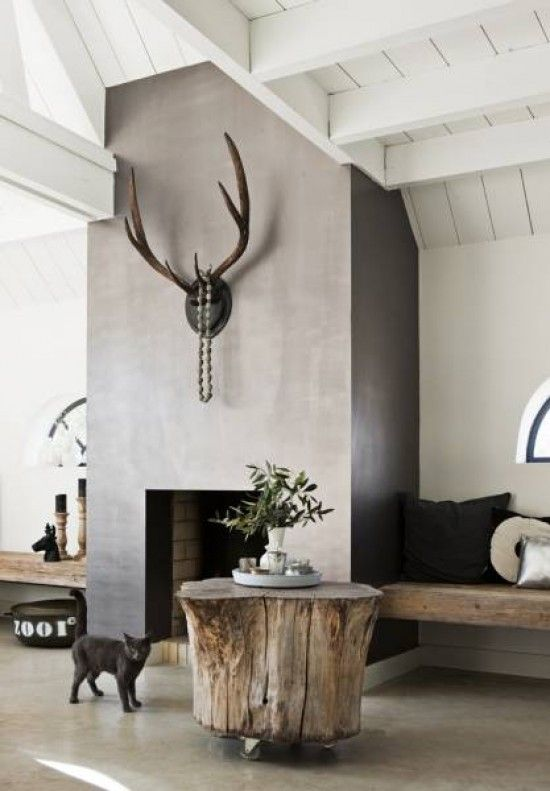 Industrial loft style living room with concrete floors, grey concrete modern fireplace and white beamed ceiling. Features a tree stump coffee table on castor wheels and antler head above the fireplace
