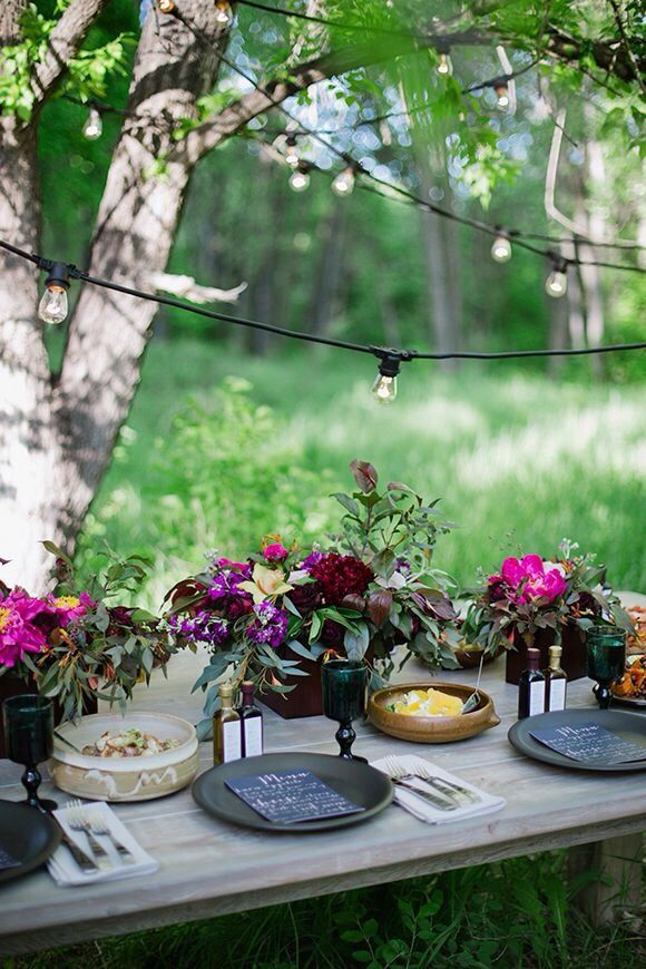 tablescape for casual outdoor dining with string lights, colorful flowers + black plates | gatherings + event ideas