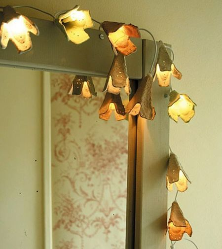 Egg cartons, a light string, and a hole punch. That's all you need to create these lovely flower lights.