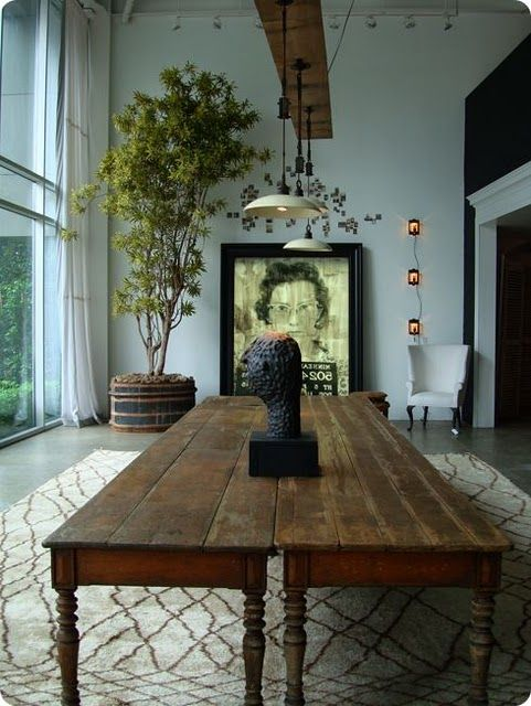 In love with these antique oak tables- and the mix of interesting art pieces- in this modern space.