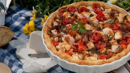 Tart with caramelized onions cherry tomatoes and manouri cheese