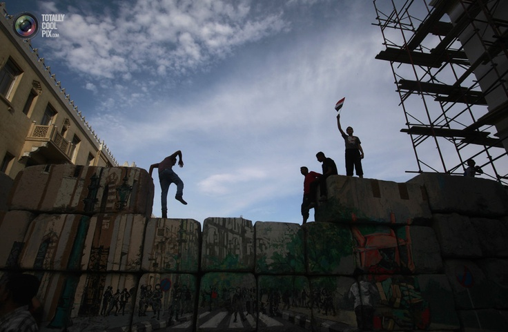 A protester waves the Egyptian flag as others walk on a wall near Tahrir square in Cairo. ASMAA WAGUIH/REUTERS