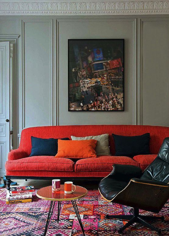 orange velvet sofa and kilim rug with eames lounge