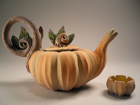 """Cinderella's Midnight Tea""  Ceramic Teapot  Created by Nancy Y. Adams  Wheel thrown porcelain teapot and cup. Hand carved and hand modeled vegetal motifs. Miniature. Lid is hand carved so as to crate a rattle,which, when shaken, rattles as if the dried seeds of the pumpkin were at hand."