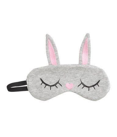Een gewatteerd slaapmasker van katoenen tricot met borduursels en een print voor en een elastieken bandje achter. Gevoerd met polyester.