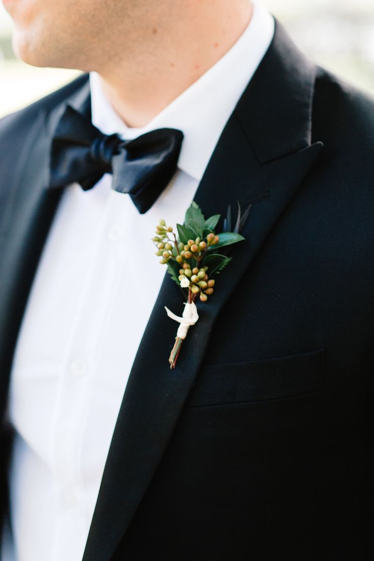 groom in classic black tuxedo wears his boutonniere of eucalyptus seeds, myrtle and burgundy agonis.