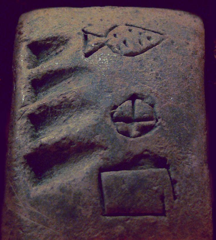 """Tontäfelchen aus Mesopotamien, 3200 v. Chr., Verwaltungstext aus Uruk (links: Zahlzeichen 4, rechts: drei Eintragungen)  Staatliche Museen zu Berlin, Vorderasiatisches Museum, VAT 14674  Fotografiert in der Ausstellung """"Am Anfang war das Formular"""", Museum für Kommunikation Frankfurt, 2008"""
