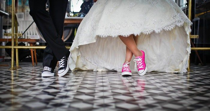 Latin Jazz Wedding Atlanta. Photo from knee to floor of shoes of bride and groom. Tennis shoes at formal event. Dancing. Jazz Wedding image.