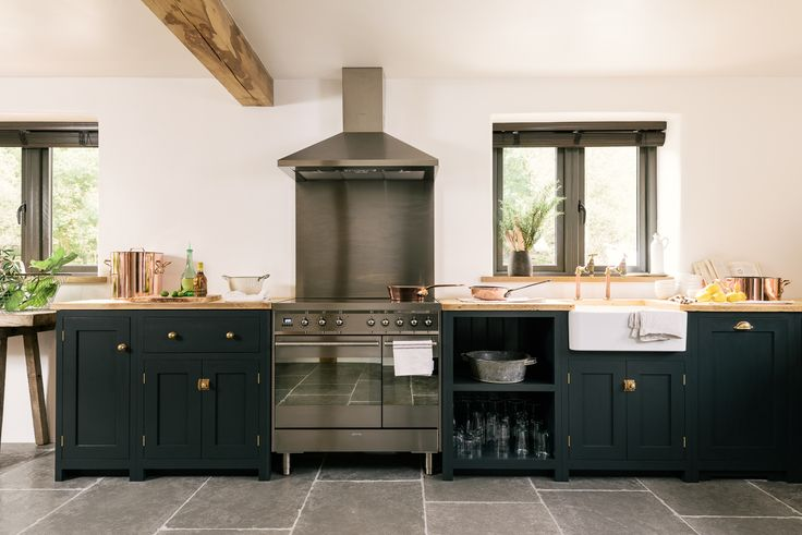 A simple run of dark blue deVOL Shaker cupboards with a Smeg range cooker