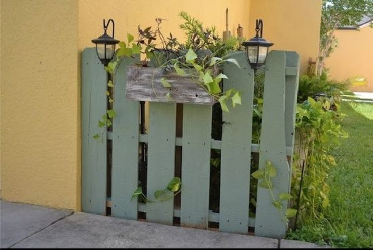 Hide trash can with a pallet...   an idea for anchoring it so it won't fall over.....drill 3 holes through the center boards (1 on the left, right, and center), then, using 3 pieces of rebar, approx 2 feet longer than the pallet, drive the rebar through the holes and into the earth.